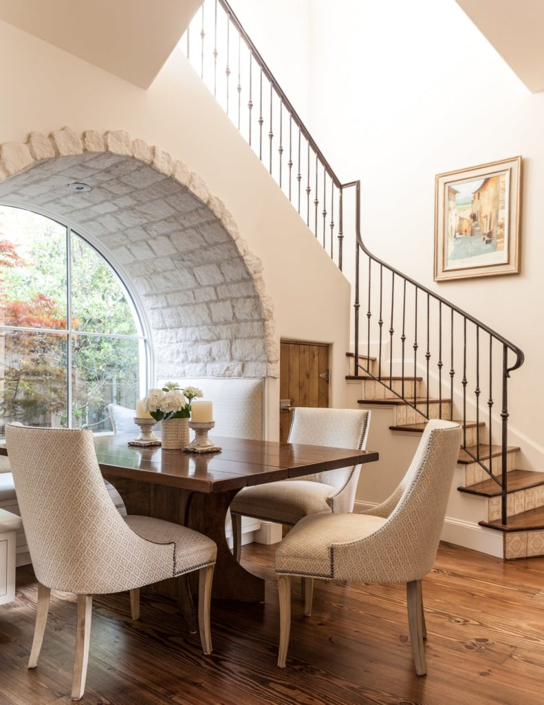 A small but cozy dining area with a wooden table, wingback chairs and a large glass arched window with a great view of the garden.