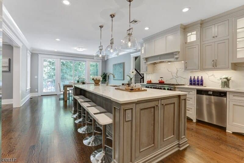 This is a rather homey and cozy kitchen with hardwood flooring paired nicely with a gray wooden kitchen island with a white countertop that matches the stools and white ceiling where three glass domed pendant lights hang.