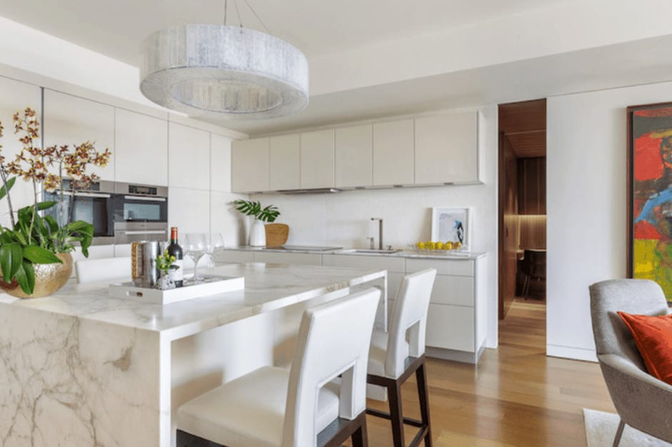 A white marble waterfall kitchen island is paired well with the white leather stools with wooden legs that complement the hardwood flooring. This island is topped with a modern round pendant light from the white ceiling.