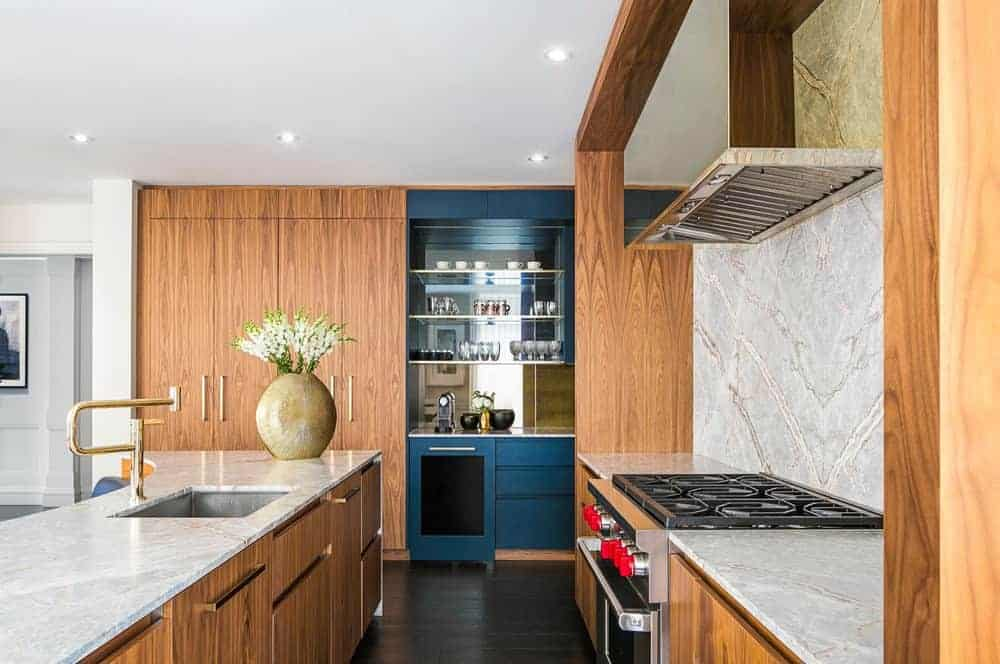This kitchen has dark wooden floors that is complemented by the wooden cabinets and drawers of the kitchen island and peninsula, both have white marble countertops that complement the modern appliances and faucet.