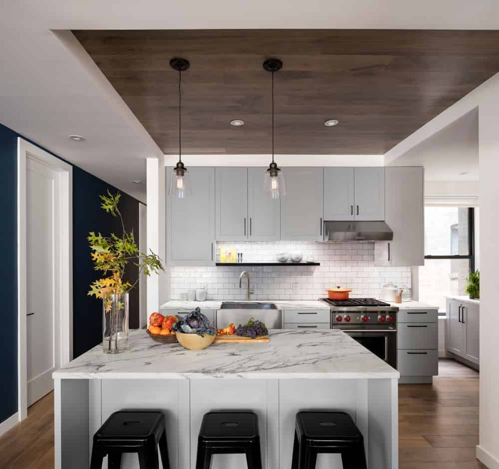 The white tray ceiling of this lovely kitchen has a wooden center tray that matches with the hardwood flooring that makes the white kitchen island stand out with its white marble countertop.