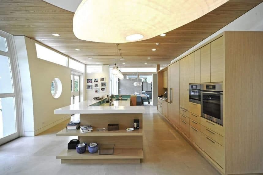 This large and airy kitchen has an L-shaped kitchen island that has built-in wooden shelves matching those of the large wooden structure dominating the wall housing the modern appliances as well as cabinets and drawers.