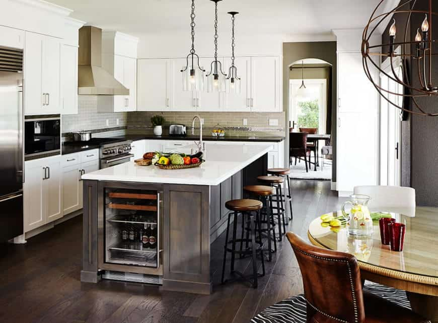 The three farmhouse-style pendant light hanging over the white countertop of the wooden kitchen island matches those stools with wooden seats and black iron legs.