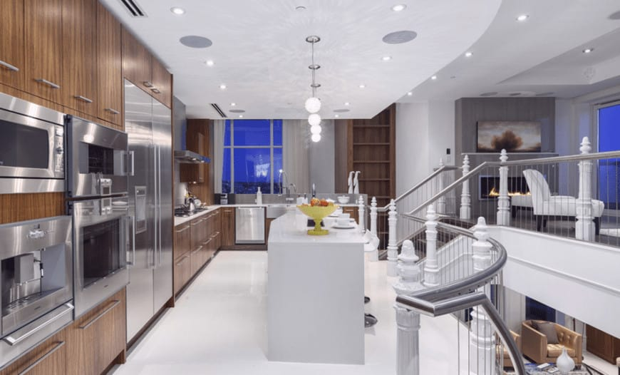 The white flooring of this kitchen is surrounded by metallic railings matching the modern appliances embedded into the wooden structure of the L-shaped kitchen peninsula contrasted by the white kitchen island.