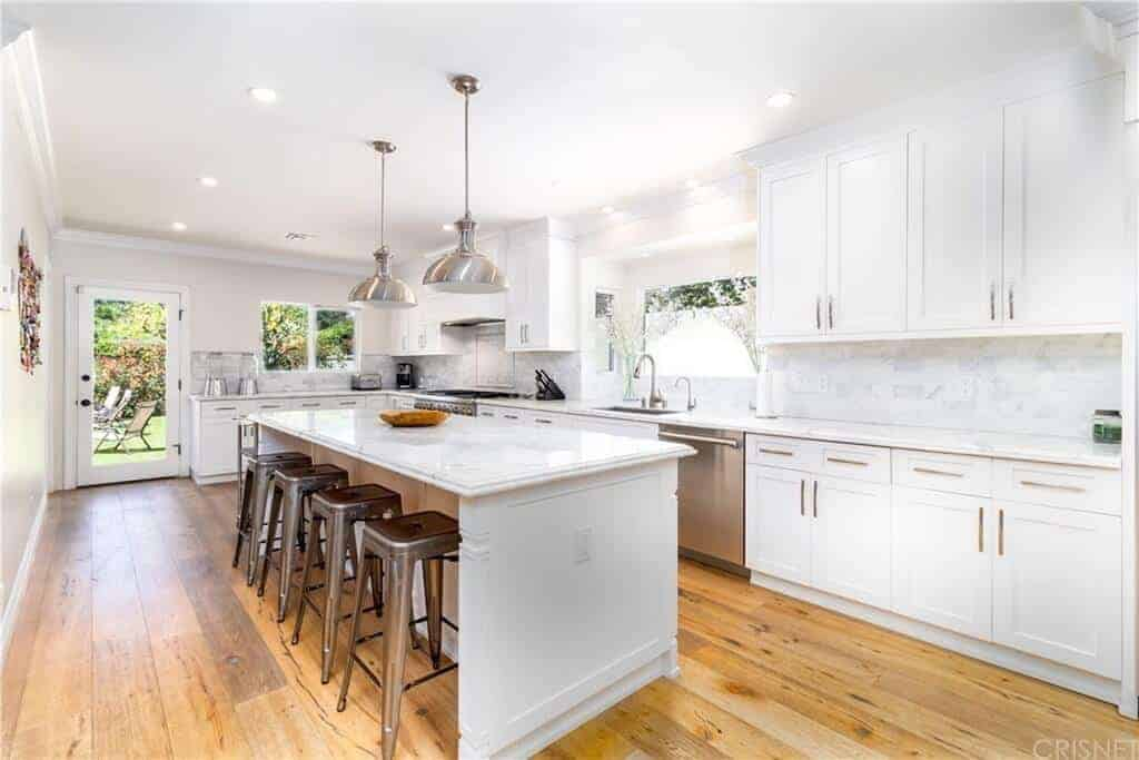 The hardwood flooring of this kitchen is contrasted by the white kitchen island and peninsula that has built-in cabinets and drawers that matches the stark white ceiling that has two silver metallic pendant lights over the island.