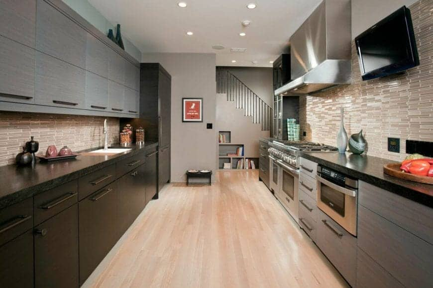 This hallway-like kitchen has two kitchen peninsulas on either side of the hardwood flooring. On one side, there is a dark theme to the cabinets and countertop while the other has a light gray theme that matches the appliances.