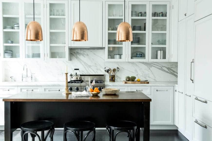 There brass dome pendant lights that look like bells hang over the wooden countertop of the black kitchen island paired with equally dark stools a dark flooring contrasting the white L-shaped kitchen island.