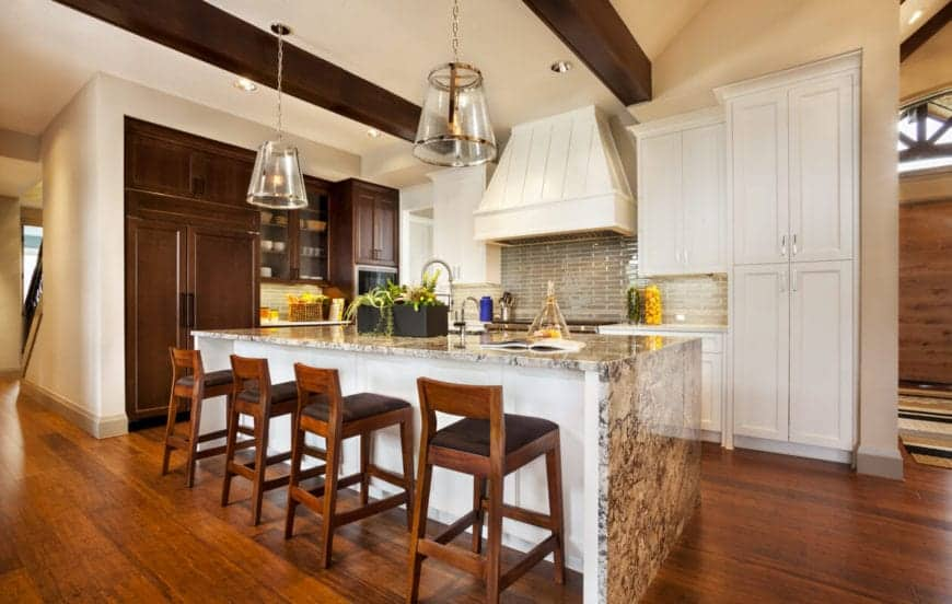 The beige ceiling has a pair of wooden exposed beams that matches the flooring and the stools of the gray marble kitchen island that has a pair of large glass pendant lights hanging over it.