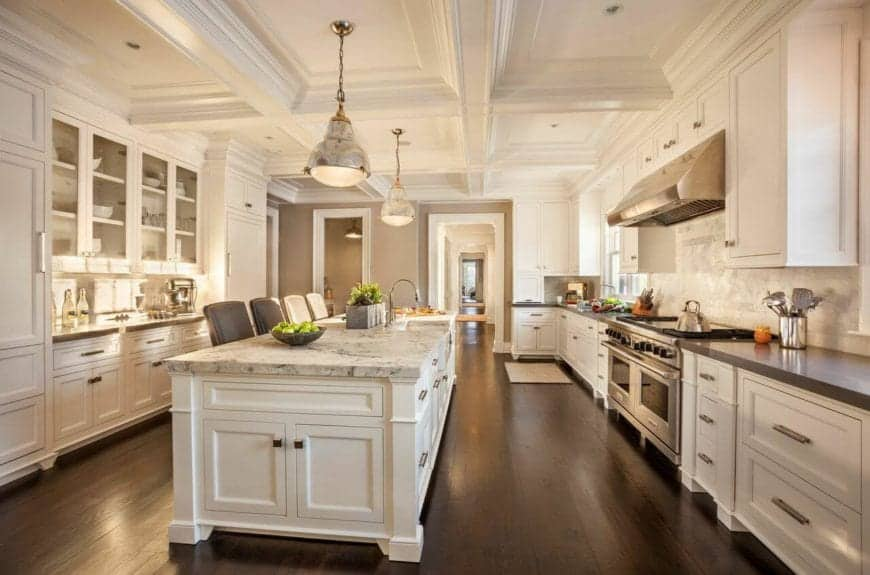 This is a large and airy kitchen with brilliant white tray ceiling that matches with the white shaker cabinets and drawers of the kitchen island and L-shaped peninsula with dark countertops making the modern appliances stand out.