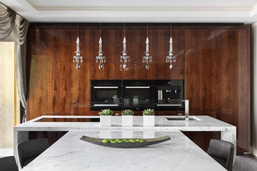 The white tray ceiling and white marble T-shaped kitchen island makes the sleek brown wood-like wall stand out with its embedded modern appliances as well as the hanging silver candle pendant lights over the kitchen island.