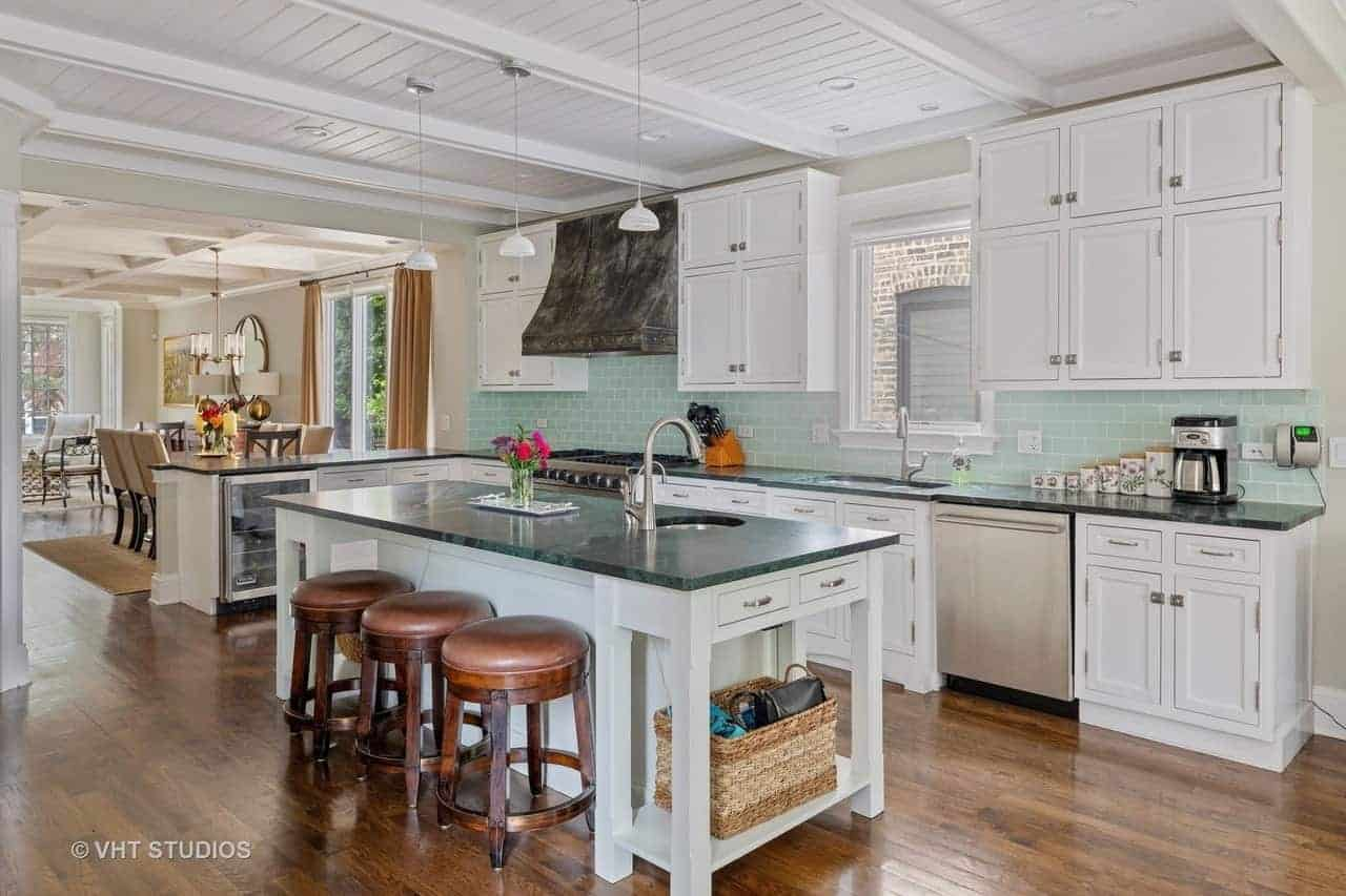The green marble countertops of the island and peninsula are complemented by the light green tiles of the backsplash paired with white cabinets and drawers that fit nicely with the white shiplap ceiling with exposed beams.