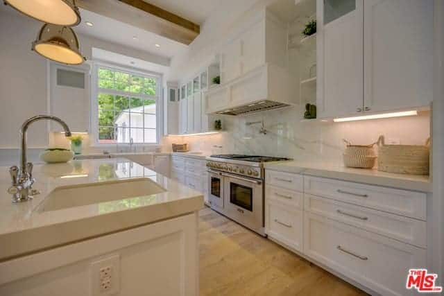 The white shaker cabinets and drawers of the kitchen island and L-shaped peninsula are topped with beige marble complementing the white marble backsplash and the hardwood flooring.
