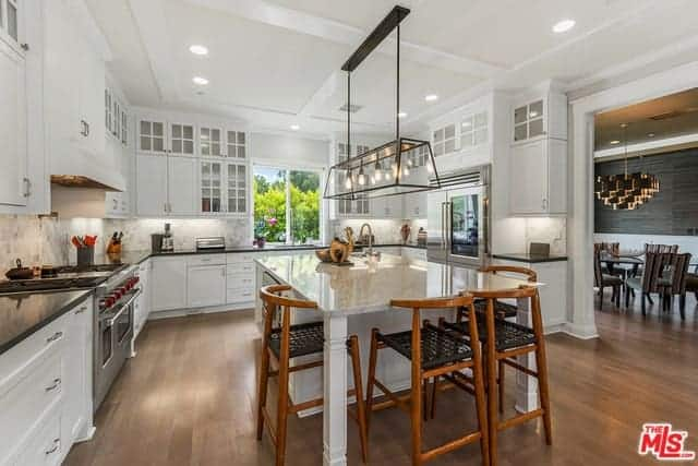 Beautiful wooden stools with woven wicker seats are paired with the beige countertop of the white kitchen island matching with the white L-shaped peninsula with black countertops that make the modern appliances stand out.
