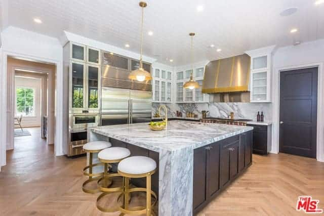 The modern white-cushioned brass stools are a nice complement to the hardwood flooring that has a herring bone pattern. This is contrasted by the cabinets and drawers of the island and peninsula under a white shiplap ceiling.