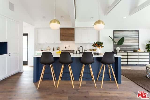 The brilliant navy blue kitchen island stands out against the hardwood flooring and the white cabinets and drawers of the kitchen as well as the white irregular arched ceiling bearing two spherical pendant lights.