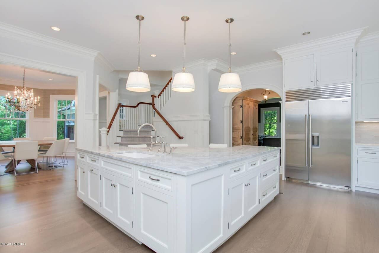 The light hardwood flooring of this kitchen is complemented by the white kitchen island illuminated by three pendant lights that pair well with the modern appliances.