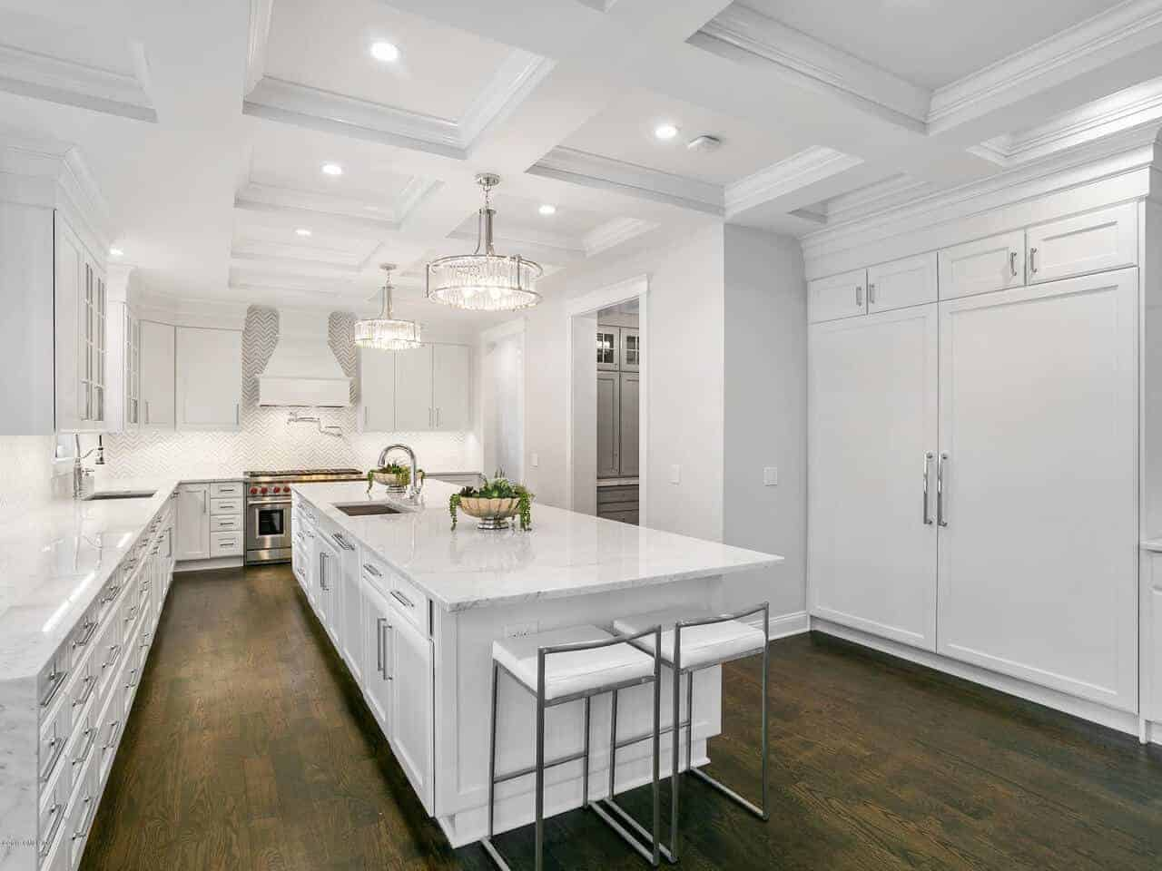 This is a predominantly white kitchen oozing with elegance in its white coffered ceiling, white kitchen island and peninsula with matching white shaker cabinets and drawers contrasted by the dark hardwood flooring.