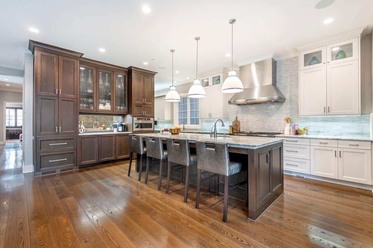 The L-shaped peninsula of this Transitional-Style kitchen is divided in two portions. One is brown that matches the hardwood flooring and the kitchen island. The other is white matching with the white ceiling and backsplash.