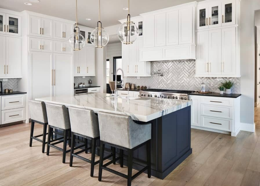 Polished white kitchen with gray wall tiles, dark blue breakfast island, white enamel cabinets with gold handles, hardwood floor, and pendant lights.