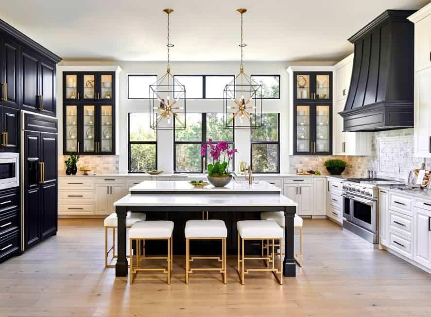 Wide sophisticated kitchen with statement pendant lights, dark blue white enamel custom cabinets, kitchen hood, breakfast island, hardwood floors, and golden accents.