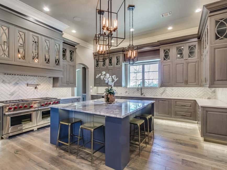 Gray aesthetic kitchen with elegant lighting, two stainless steel ovens, gray enamel custom cabinets, breakfast island in blue with marble countertop, and hardwood floors.