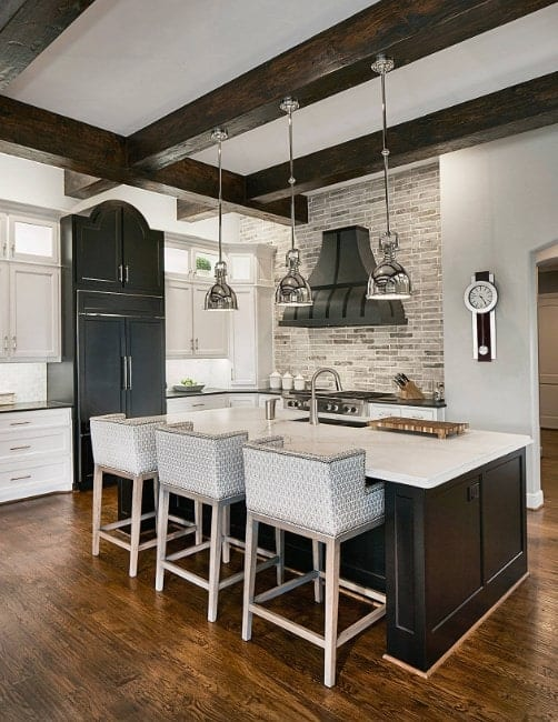 L-shaped kitchen with breakfast island, pendant lights, visible wooden beams from the ceiling, brick walls, and hardwood floors.