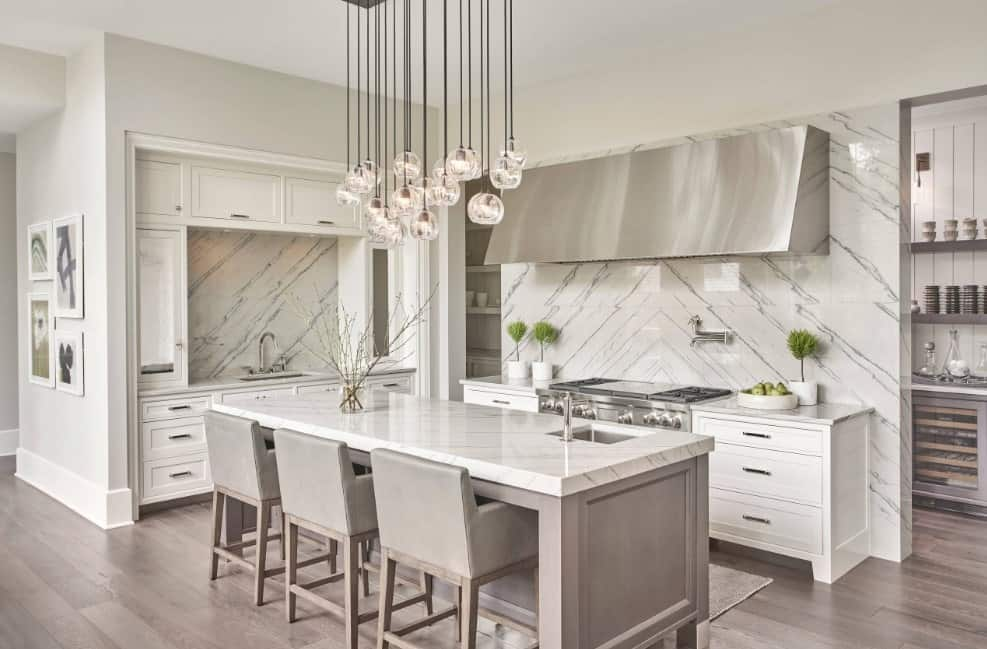 White luxurious kitchen with marble countertop breakfast island, stainless steel hood and appliances, statement chandelier, white enamel cabinets, and grayish hardwood floors.