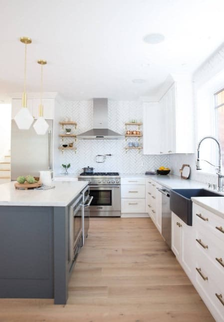 Chic bright white kitchen with white enamel drawers, kitchen island, pendant lights, and stainless steel appliances.