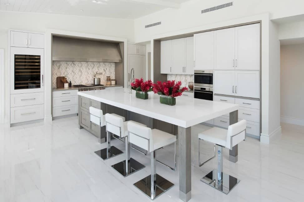 White polished kitchen with elegant breakfast island, white floor tiles, white enamel cabinets, stainless steel appliances, and recessed ceiling lights.