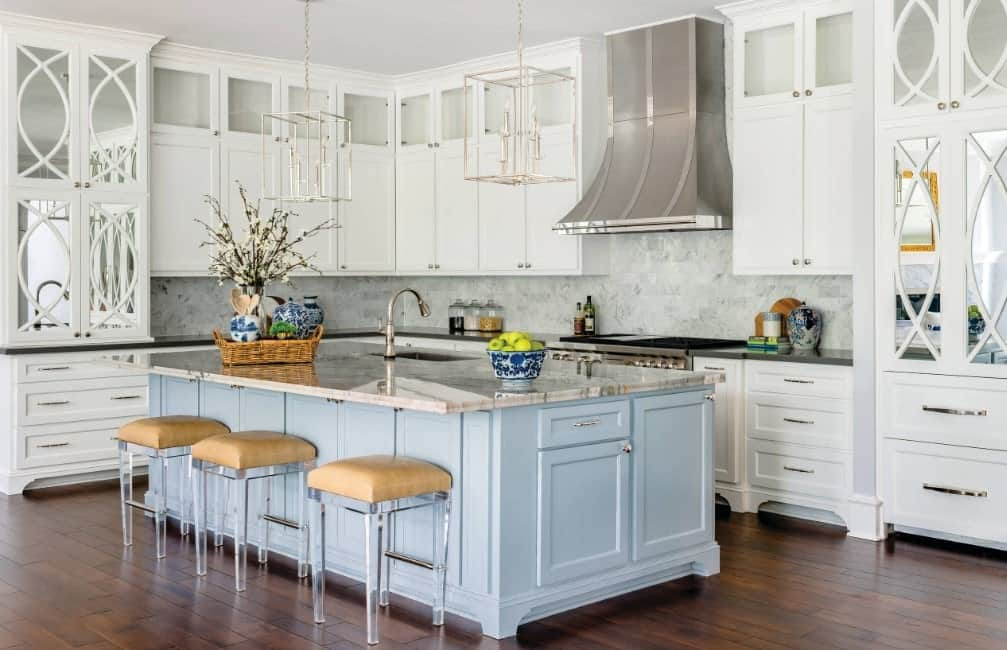 Decorative L-shaped kitchen with white enamel cabinets, a touch of pastel blue hue from the breakfast island, unique pendant lights, kitchen hood, and hardwood floors.
