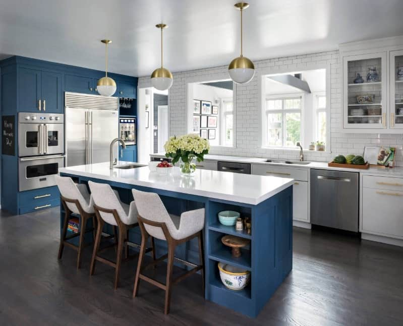 Stylish L-shaped kitchen with blue cabinets, stainless steel appliances, simple round pendant lights, white brick walls, hardwood floors, and a blue breakfast island.