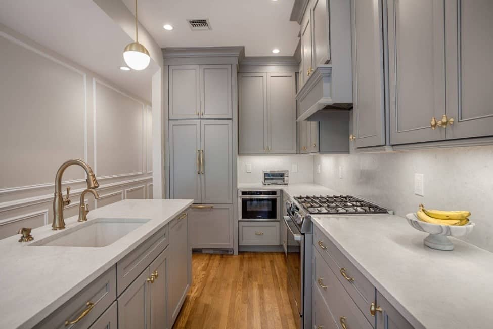 U-shaped kitchen in gray enamel custom cabinets, gold accents, hardwood floors, recessed lighting, and simple pendant lighting.