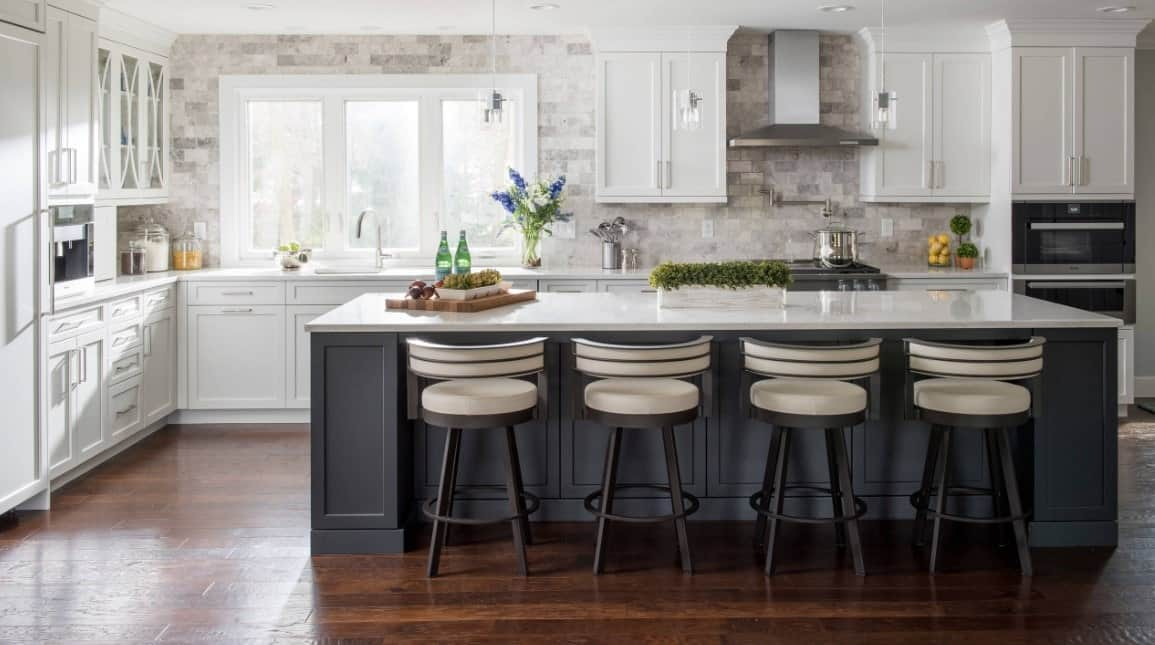 White L-shaped kitchen with dark gray breakfast island, white enamel cabinets, hardwood floors, and pendant lights.