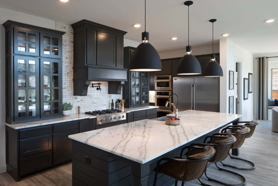 Residential kitchen with marble countertop breakfast island, simple pendant lights, stainless steel appliances, dark enamel cabinets, and hardwood floors.
