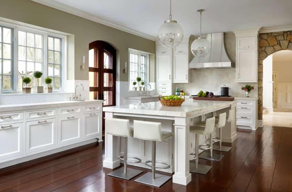 Elegant residential kitchen with white custom enamel cabinets, polished hardwood floors, breakfast island, and pendant lights.