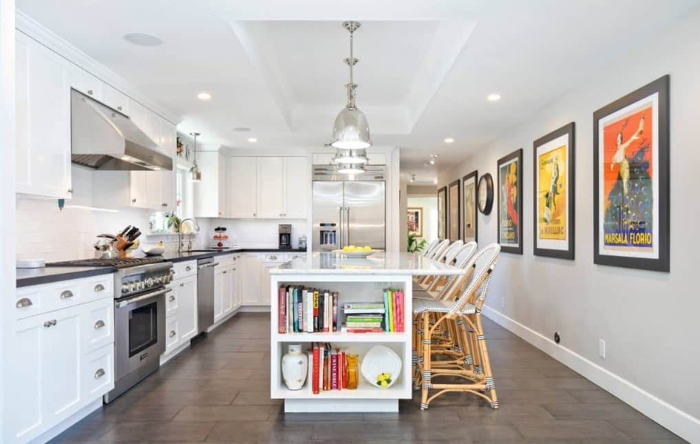 White L-shaped stylish kitchen with retro decor, breakfast island, pendant lights, cookbook shelf, and stainless steel appliances.