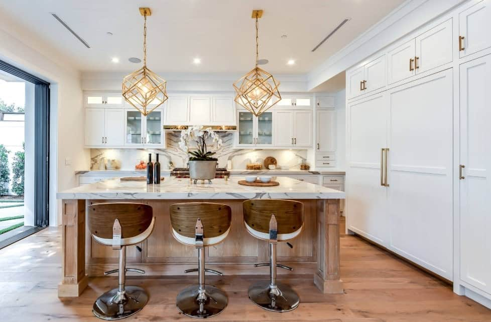 White aesthetic kitchen with rustic accents, gold pendant lights, breakfast island, white enamel cabinets, and hardwood floors.