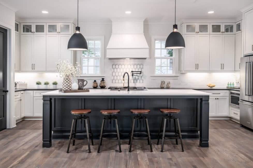 Elegant white kitchen with breakfast island, white cabinets, stainless steel appliances, hardwood floors, a kitchen hood, and simple pendant lights.