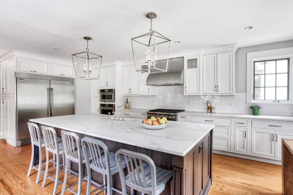 A clean white kitchen with huge stainless steel refrigerator, breakfast island, marble countertops, hardwood floors, and pendant lights.