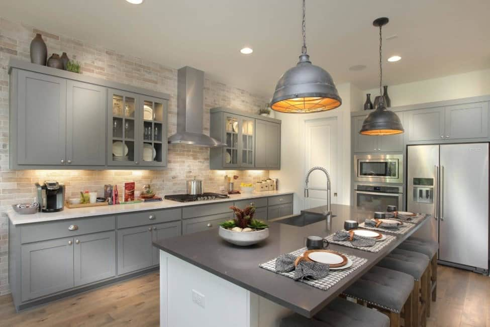 Gray and neutral tones kitchen with breakfast island, beige wall tiles, hardwood floors, and gray pendant lights.