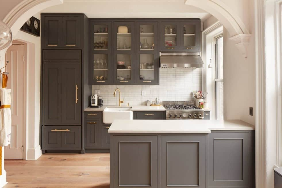 Kitchen room with dark gray custom cabinets in gold accents, stainless steel appliances, kitchen hood, and hardwood floors.