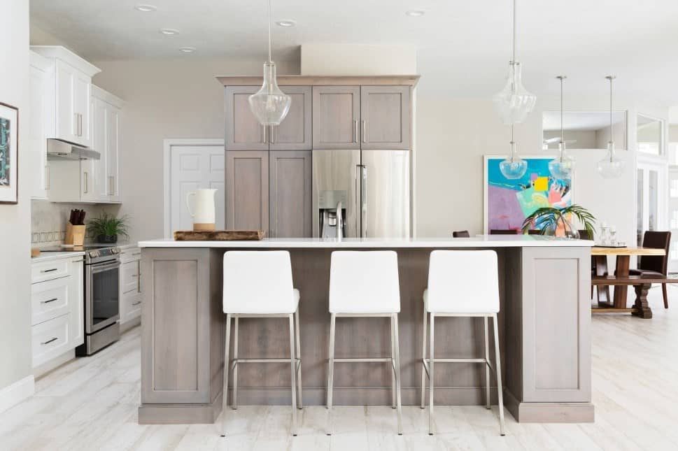 Polished white and gray kitchen with breakfast island, light hardwood floors, rustic gray cabinets, and glass pendant lights.