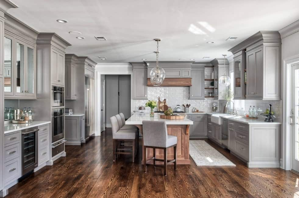 Vast gray kitchen with gray custom enamel cabinets, hardwood floors, stainless steel appliances, wooden breakfast island, and glass pendant lights.