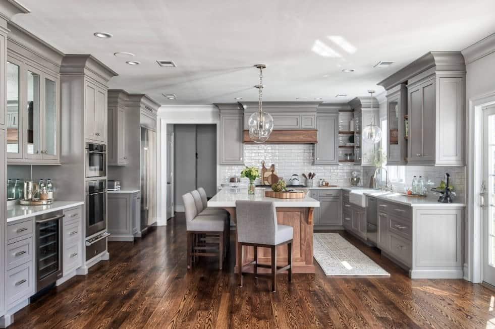 Vast gray kitchen with gray custom enamel cabinets, hardwood floors, stainless steel appliances, wooden breakfast island, and glass pendant lights.