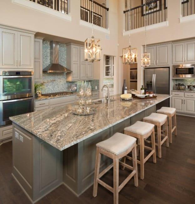 Elegant kitchen in neutral tones, with long gray breakfast island, stylish upholstered stools, hardwood floors, and stylish pendant lights.