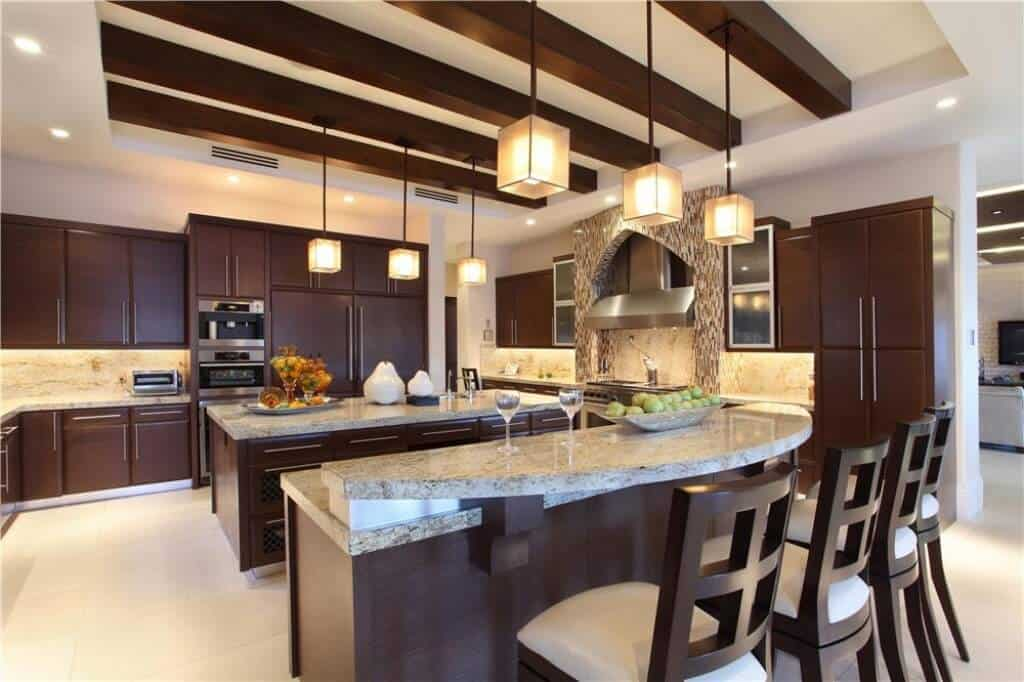 The sleek white tray ceiling has exposed wooden beams in the middle tray. This matches with the dark wooden kitchen islands and peninsulas with gray marble countertops as well as a second tire bar that is paired with wooden chairs.