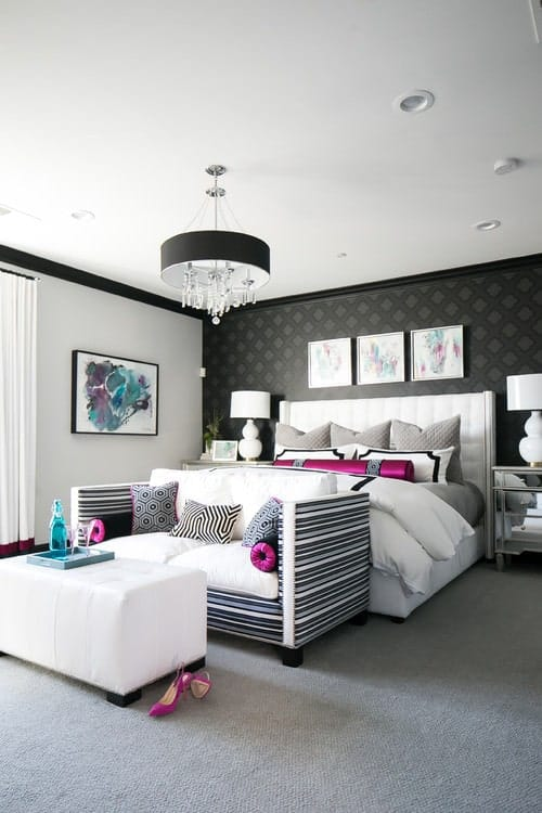 Glamorous master bedroom with a black diamond-patterned wallpaper highlights the white bed with a striped loveseat at its end. It is illuminated by a black drum chandelier that hung from a white ceiling.