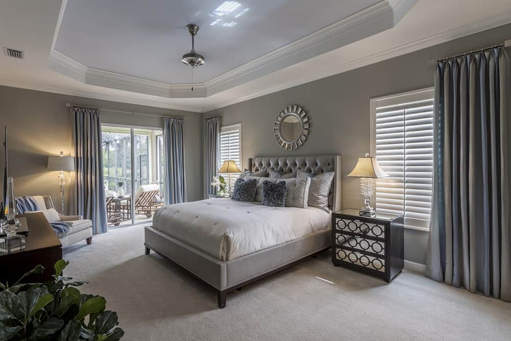 A small unique chandelier hung from a tray ceiling in this gray transitional master bedroom. It features a round mirror that's mounted above the bed, carpet flooring, and glass door that leads to the patio area.
