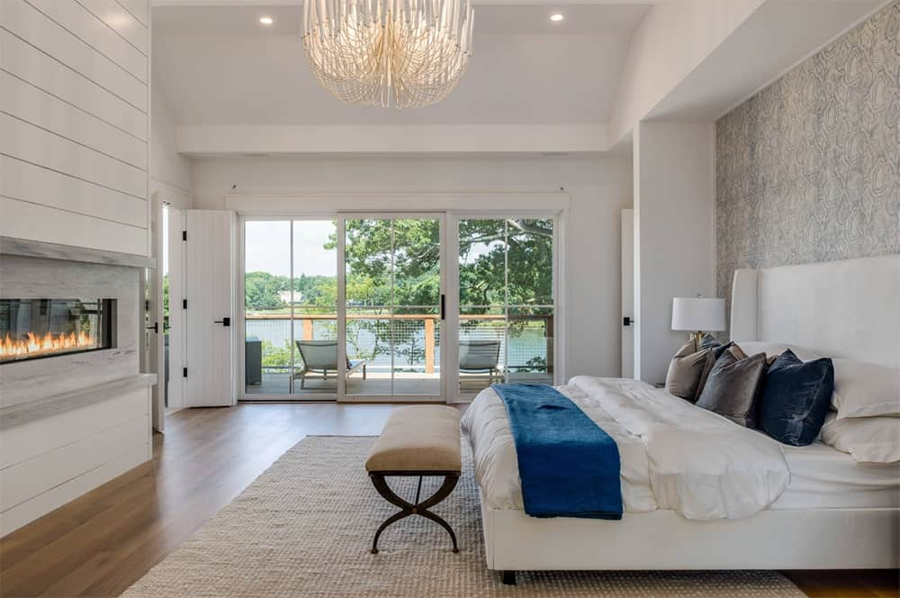 Stunning master bedroom features a white upholstered bed facing a modern fireplace that's mounted on a shiplap wall along with a fancy chandelier.