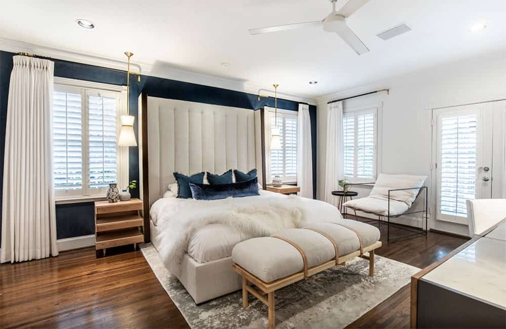 Gorgeous transitional master bedroom features a navy blue accent wall that matches the velvet pillows. It has an oversized upholstered headboard lighted by a pair of fancy brass pendant lights.